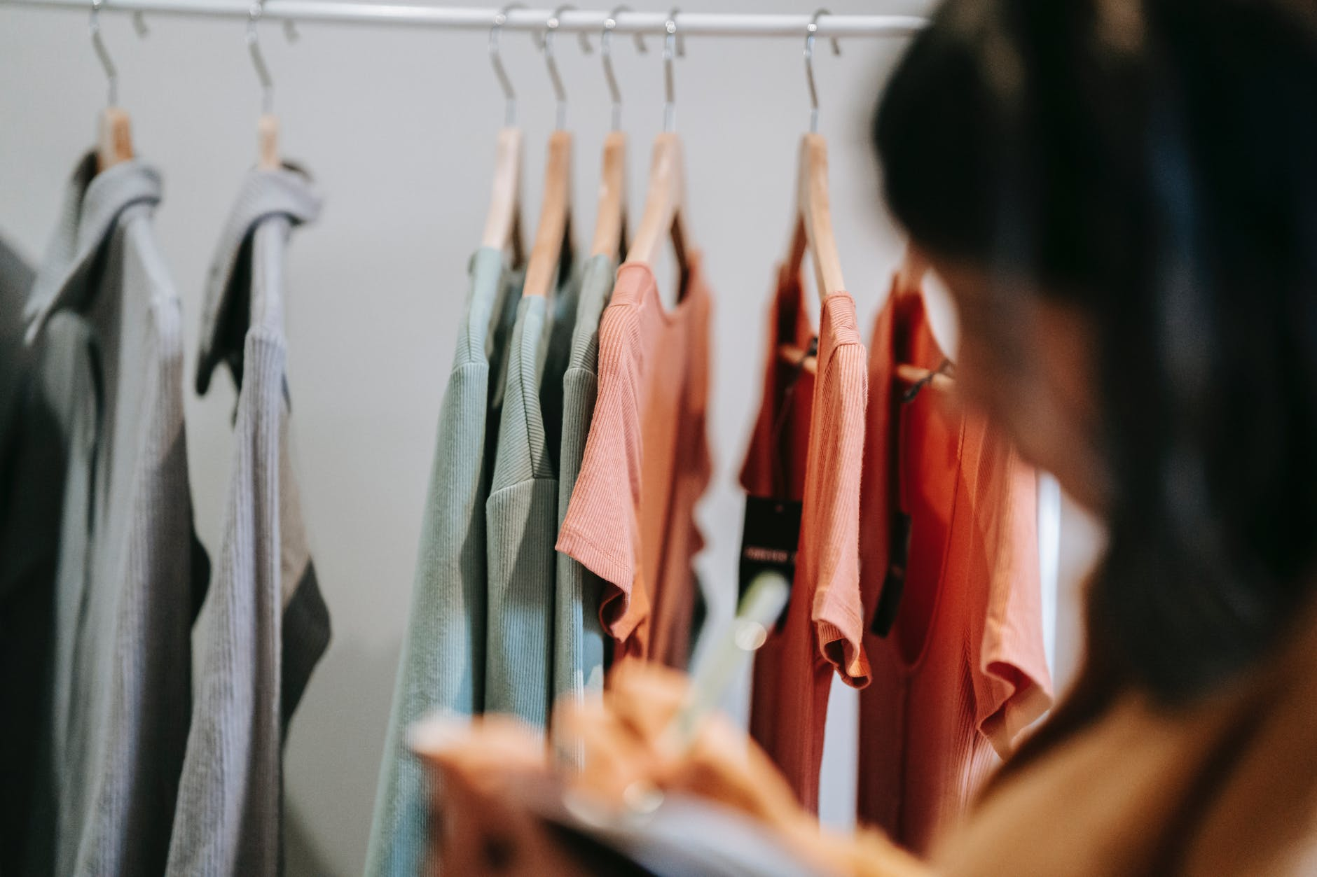 crop designer writing against assorted outfit on rack
