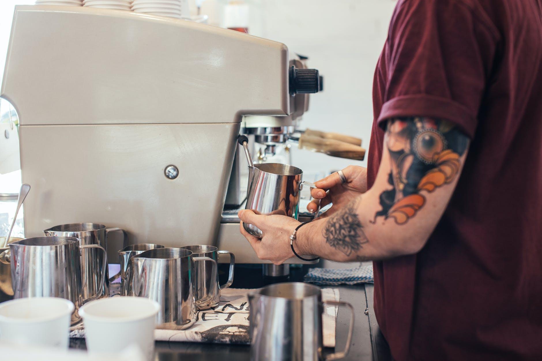 tattooed barista making coffee with coffee machine