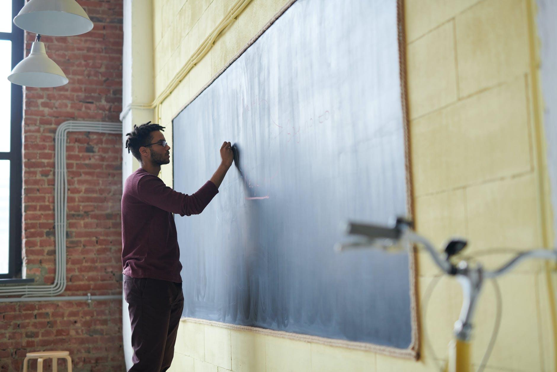 man writing on a blackboard